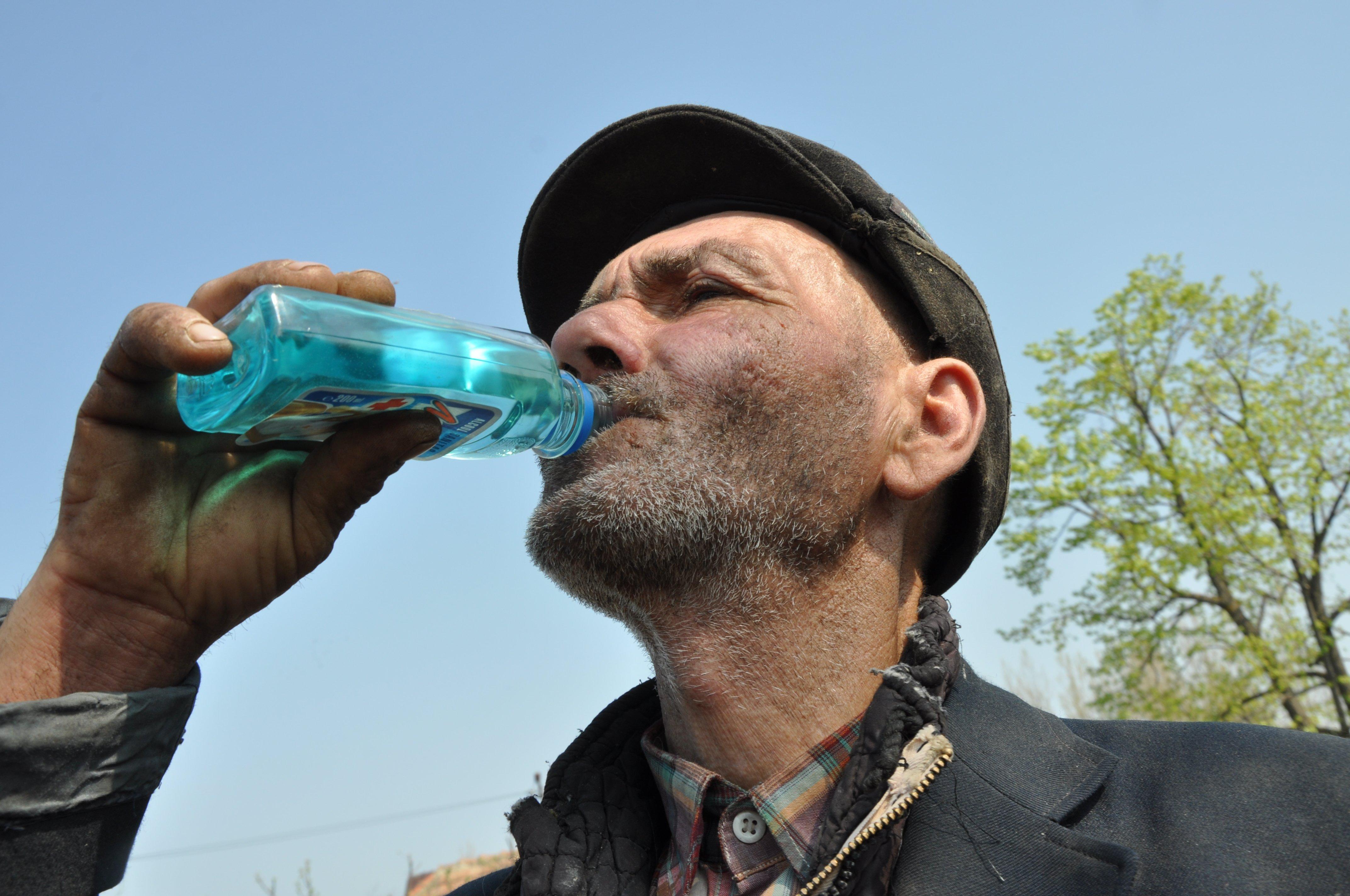 """Omul bea spirt medicinal! Bea cum aş beau eu apă. Alcool sanitar """"Mona"""". Când ridică sticluţa la gură, parcă n-ar avea nimic în mână. Cum e cerul de albastru, aşa e şi spirtul. (Foto: V. I.)"""